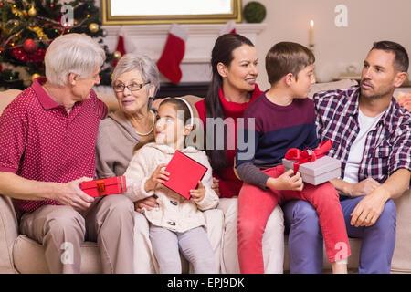 Multi generation family holding presents on sofa - Stock Photo