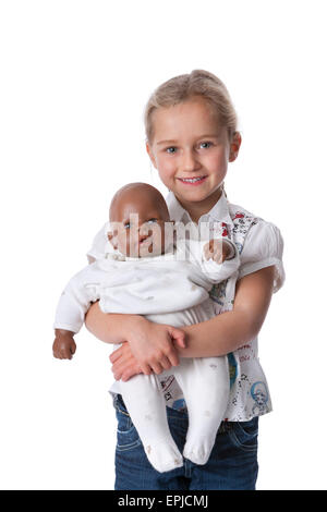 Portrait of a five year old blond girl with her ethnic baby doll on white background and space for text - Stock Photo