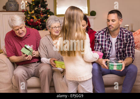 Cute little girl offering gift to her family - Stock Photo
