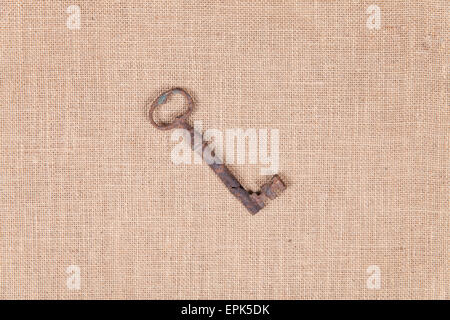 18th century antique key over a sackcloth texture - Stock Photo