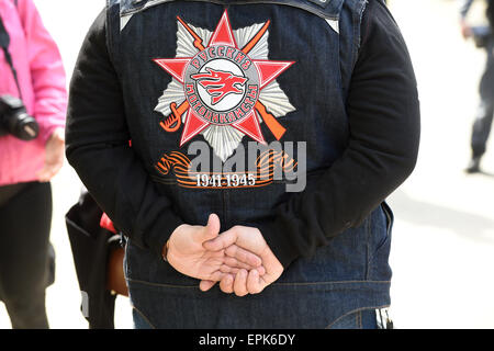 A member of the Russian motorcycle club 'Nachtwoelfe' (lit. Night wolves) wears a jacket with its logo and ribbons - Stock Photo