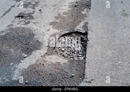 Pothole in road after spring thaw - Stock Photo