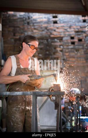 Female welder working in metal workshop - Stock Photo