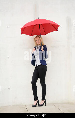 Smiling businesswoman with red umbrella leaning on concrete wall - Stock Photo