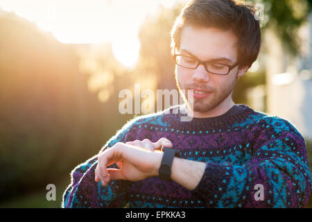 Portrait of young hipster using smartwatch at backlight - Stock Photo