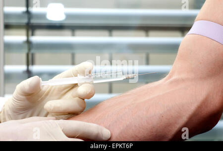 Man receiving injection in arm - Stock Photo