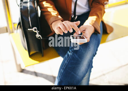 Woman waiting at the bus stop using smartphone - Stock Photo