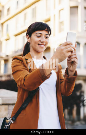 Spain, Barcelona, smiling businesswoman taking selfie with smartphone - Stock Photo