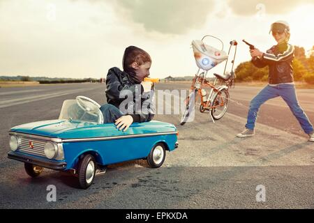 Two boys playing cops and robbers - Stock Photo