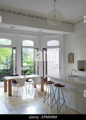 Breakfast Bar Stools And Small Dining Table In White Kitchen With Open Glass Doors Leading