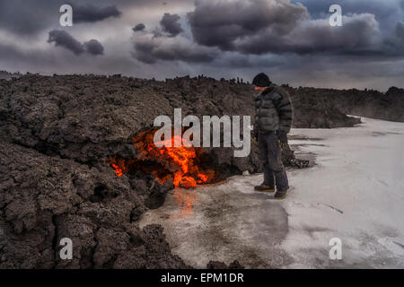 Man standing by glowing lava flow, Holuhraun Fissure Eruption, Bardarbunga Volcano, Iceland - Stock Photo