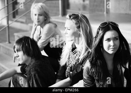 Young fashion people sitting on the steps - Stock Photo