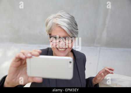 Portrait of smiling career woman taking a selfie with smartphone - Stock Photo
