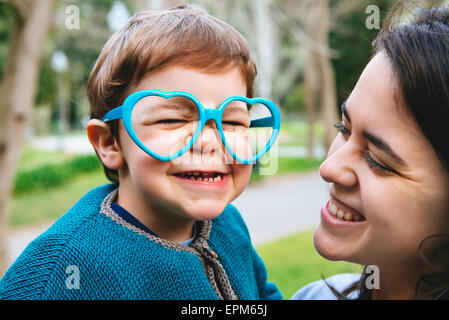 Portrait of little boy making faces with heart shaped glasses - Stock Photo