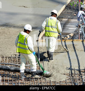 Close up building construction industry site workers placing & vibrating pumping concrete into reinforcement floor - Stock Photo