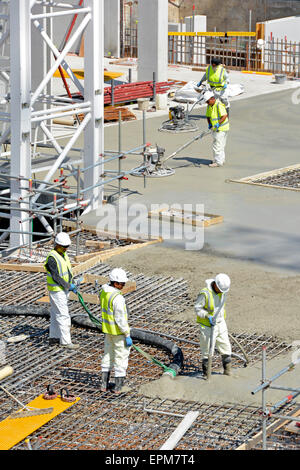 Placing & vibrating pumped concrete into steel reinforcement with power float operators following finishing smooth - Stock Photo