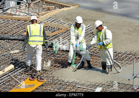 Placing & vibrating pumped concrete into steel reinforcement on new floor slab for apartment block - Stock Photo