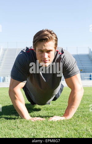 USA, California, San Luis Obispo, portrait of young man doing pushups on an athletic field - Stock Photo
