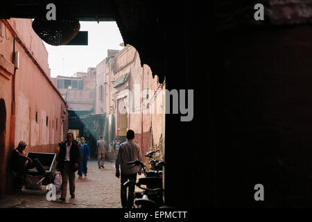 Locals walking on a market street in the medina (old town) of Marrakech in Morocco - Stock Photo