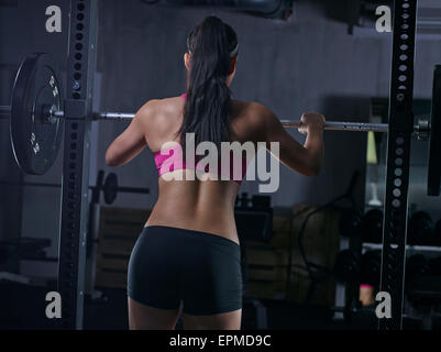 Rear view of young woman doing weightlifting with barbell - Stock Photo