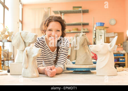 Portrait of potter surrounded by dog figurines - Stock Photo