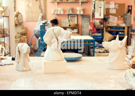 Ceramic dog figurines in potter's workshop - Stock Photo