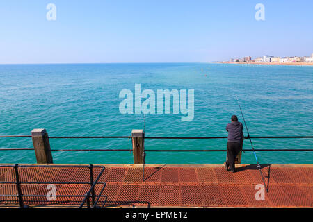 Man casually leaning on railings of Worthing Pier fishing - Stock Photo