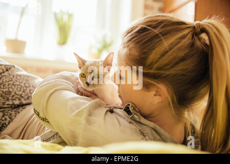 Woman with Burmese cat at home - Stock Photo