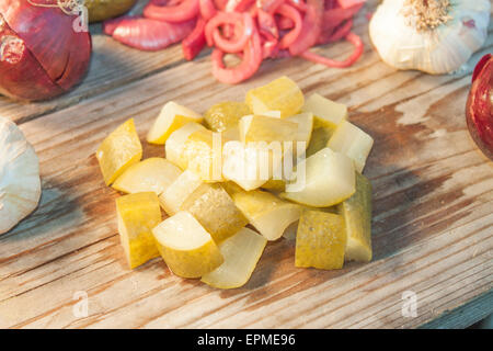 A pile of pickled cucumber dice, in front of garlic and red onion - Stock Photo