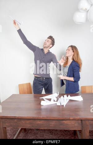 Two colleagues playing with paper planes - Stock Photo
