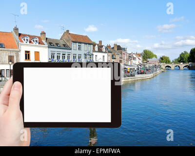 travel concept - tourist photograph Quai Belu on Somme river in Amiens city, France on tablet pc with cut out screen - Stock Photo
