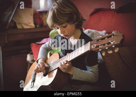 Portrait of little boy playing acoustic guitar at home - Stock Photo