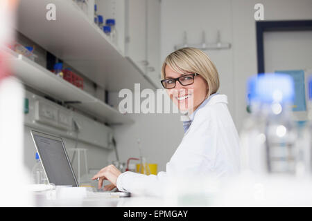 Smiling scientist using laptop in laboratory - Stock Photo
