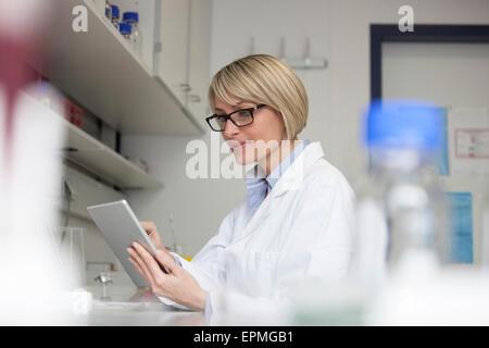 Scientist using digital tablet in laboratory - Stock Photo