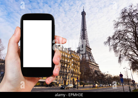 travel concept - tourist photograph eiffel tower from quai branly in Paris on sunset on smartphone with cut out - Stock Photo