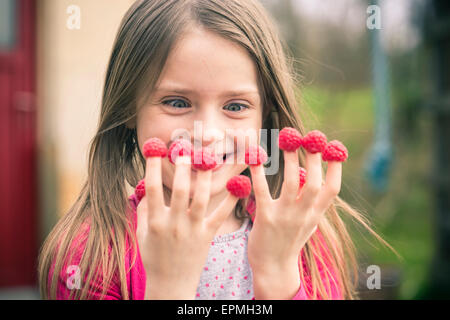Happy girl with raspberries on her fingers - Stock Photo