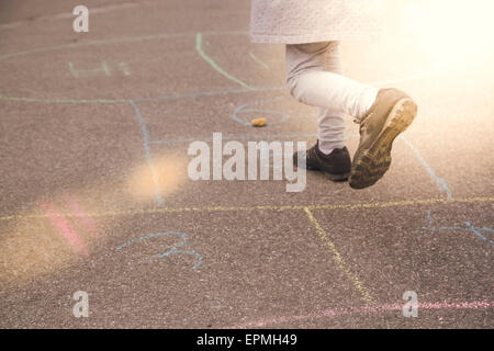 Little girl playing hopscotch - Stock Photo