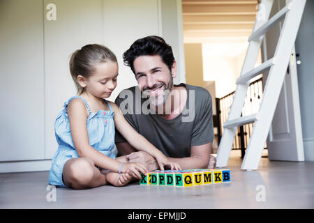 Father and daughter playing with building bricks on the floor - Stock Photo