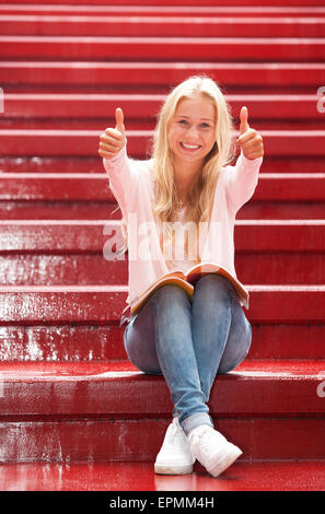 Portrait of smiling female teenager showing thumbs up - Stock Photo