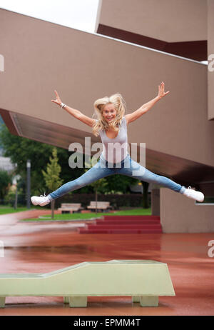 Portrait of blond teenage girl jumping in the air with outstretched arms and legs - Stock Photo