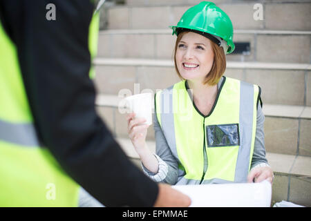 Manager and foreman discussing construction project on site - Stock Photo