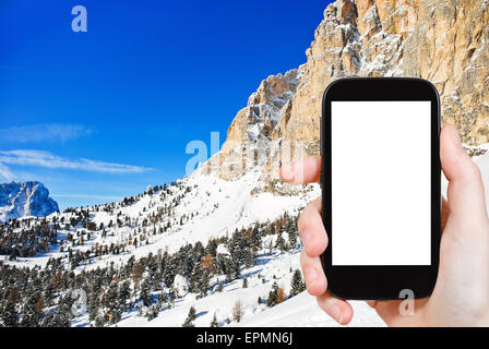 travel concept - tourist photograph slope of Dolomites mountain in Val Gardena, Italy on tablet pc with cut out - Stock Photo