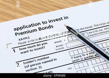 Application form to invest in Premium Bonds and a black ballpoint pen for completing the investment paperwork.  - Stock Photo