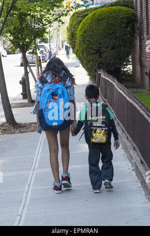 Teen girl walks home after school with her younger brother in Brooklyn; NY. - Stock Photo