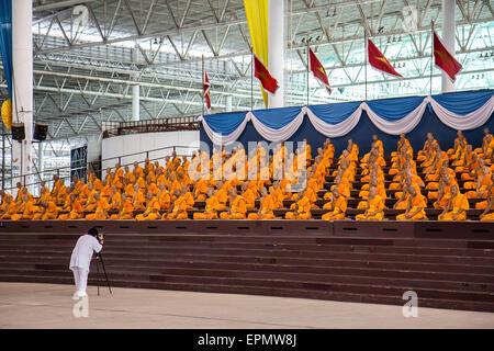 Man photographing praying monks at the Wat Phra Dhammakaya - Stock Photo