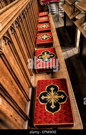 Embroidered kneelers, hassocks or prayer cushions on a pew in St Mary the Virgin Church, Oxford, England, UK. - Stock Photo