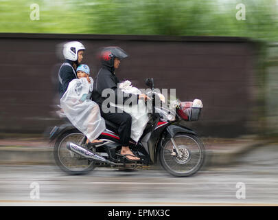 Asian family rides in the rain on a motorcycle - Stock Photo