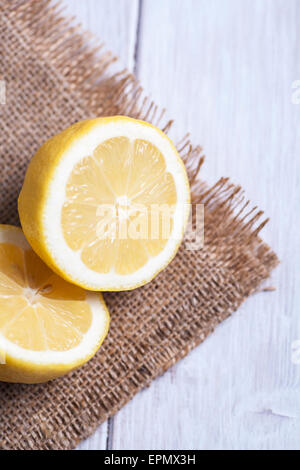 Lemon cut in half and sat on hessian material - Stock Photo