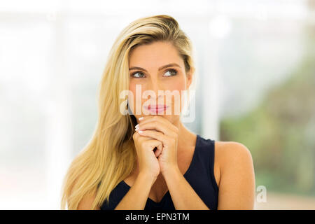 thoughtful young blond woman looking up - Stock Photo