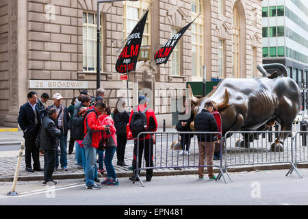 Tourists pose for pictures by the Charging Bull statue on Broadway in the Financial District of New York City. - Stock Photo